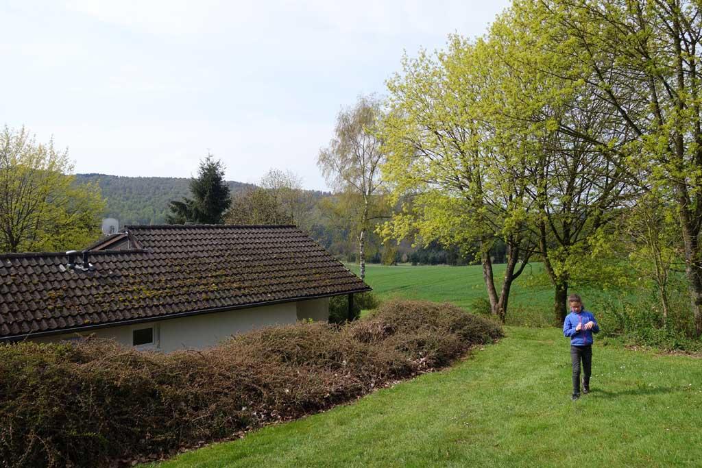 Roos loopt via het pad achter het huisje naar de speeltuin.