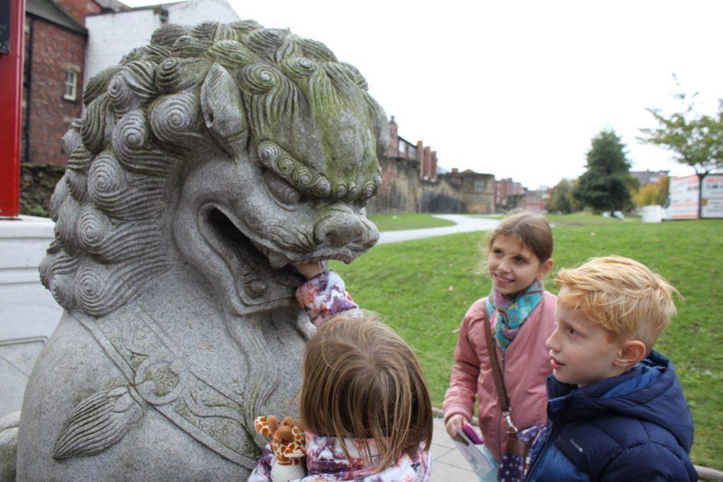 Bij de toegangspoort van Chinatown proberen we de bal uit de bek van dit enge beest te krijgen.