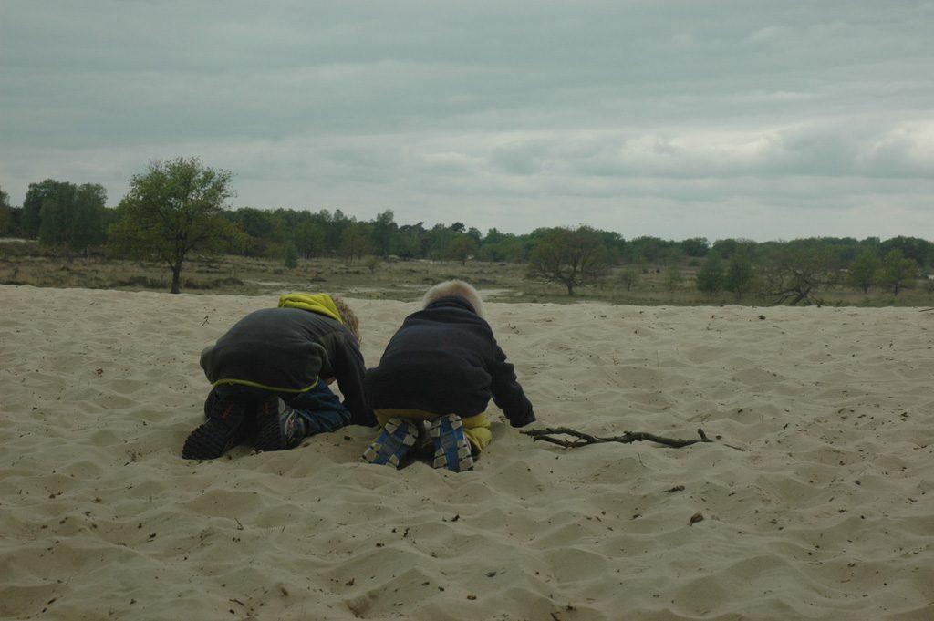Spelen met zand in de grote zandbak.