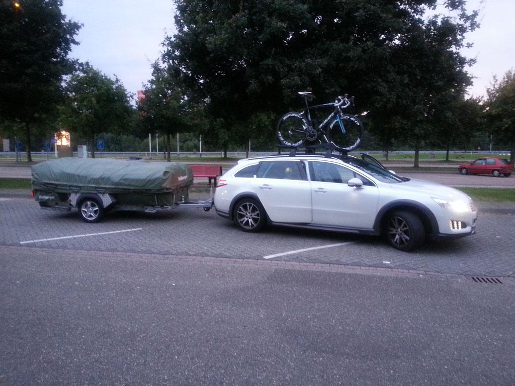 Met de vouwwagen achter de auto.