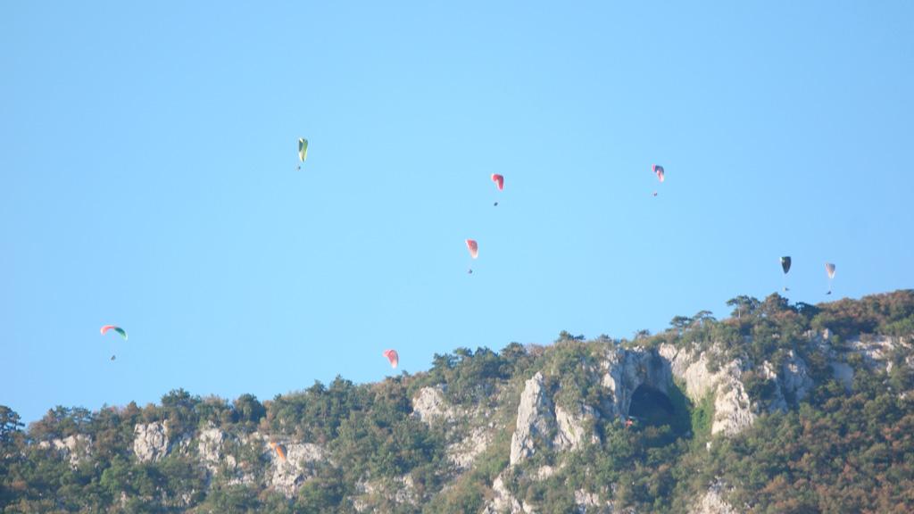De paragliders vertrekken vanaf een veldje op een berg vlakbij de camping.