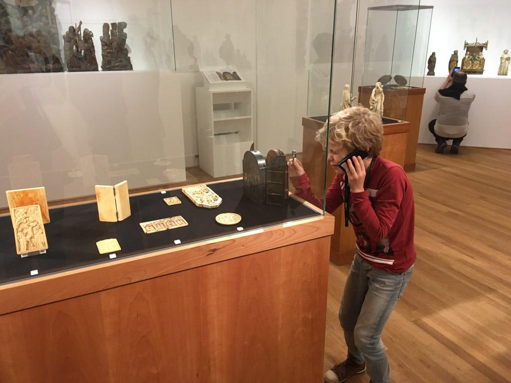 Faas onderzoekt met zijn mini-vergrootglas de oude voorwerpen in de vitrine
