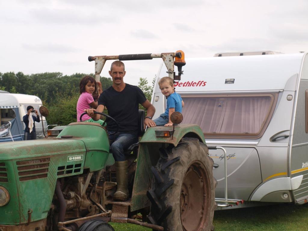 Boer Peter brengt de caravan naar de kampeerplek. Kinderen mogen mee op de trekker.
