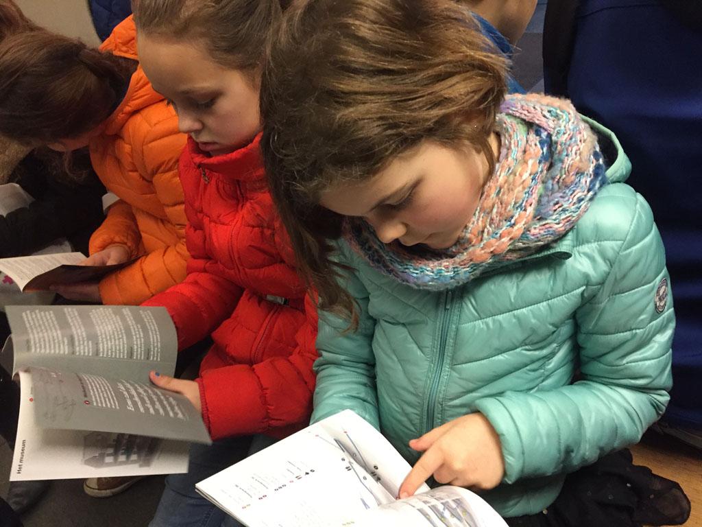 Wachten voordat de lezing begint. Ondertussen de brochure over het Anne Frank Huis lezende.