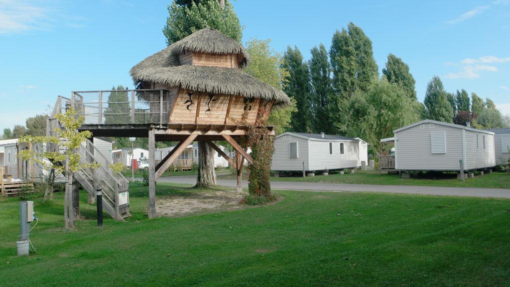 Onze mobil home staat naast deze boomhut.