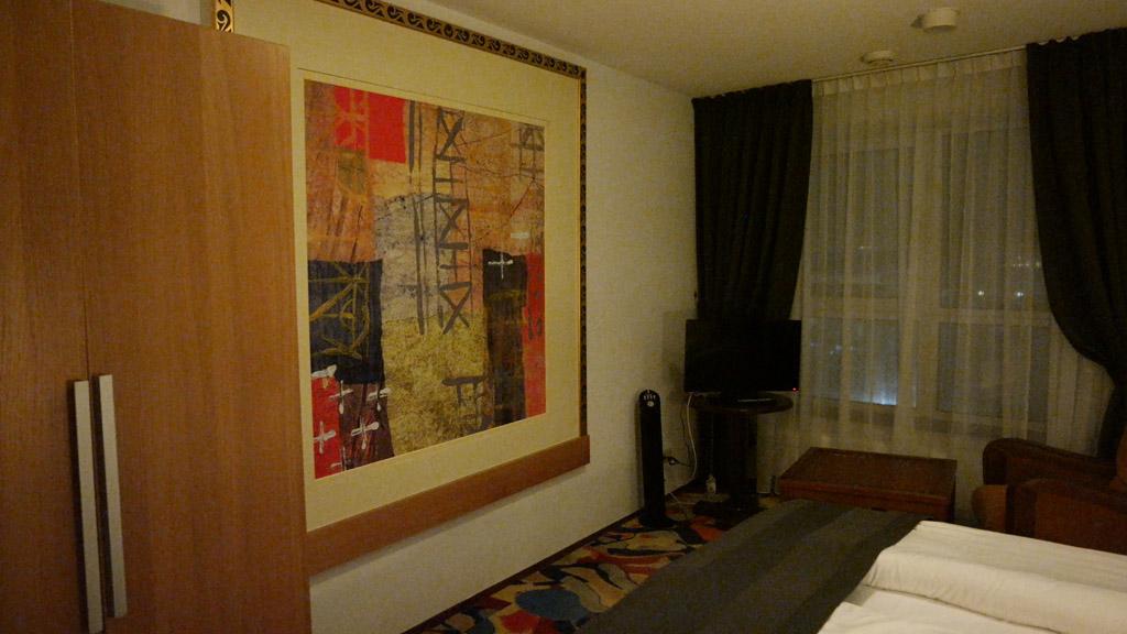 Groot kunstwerk aan de muur en een klein zitje bij de tv.