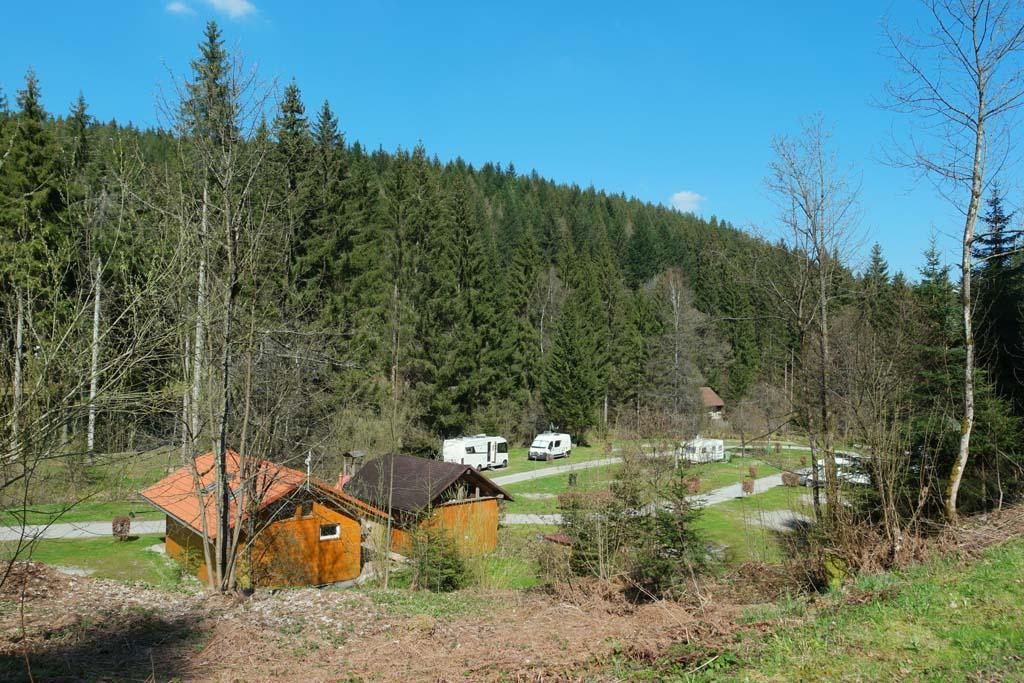 Links voor het achterste sanitair gebouw van Camping Langenwald en rechts enkele kampeerplekken.