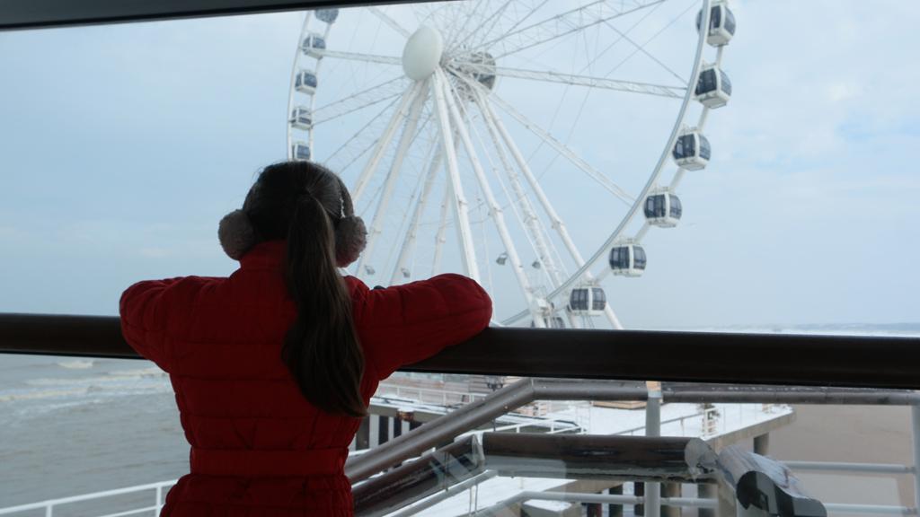 Maureen bestudeert het reuzenrad op de Pier van Scheveningen.