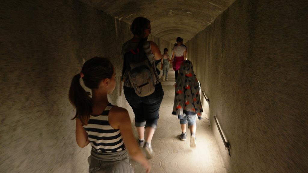 Via een gang lopen we naar de grot. Daarna moeten we de fotocamera opbergen.
