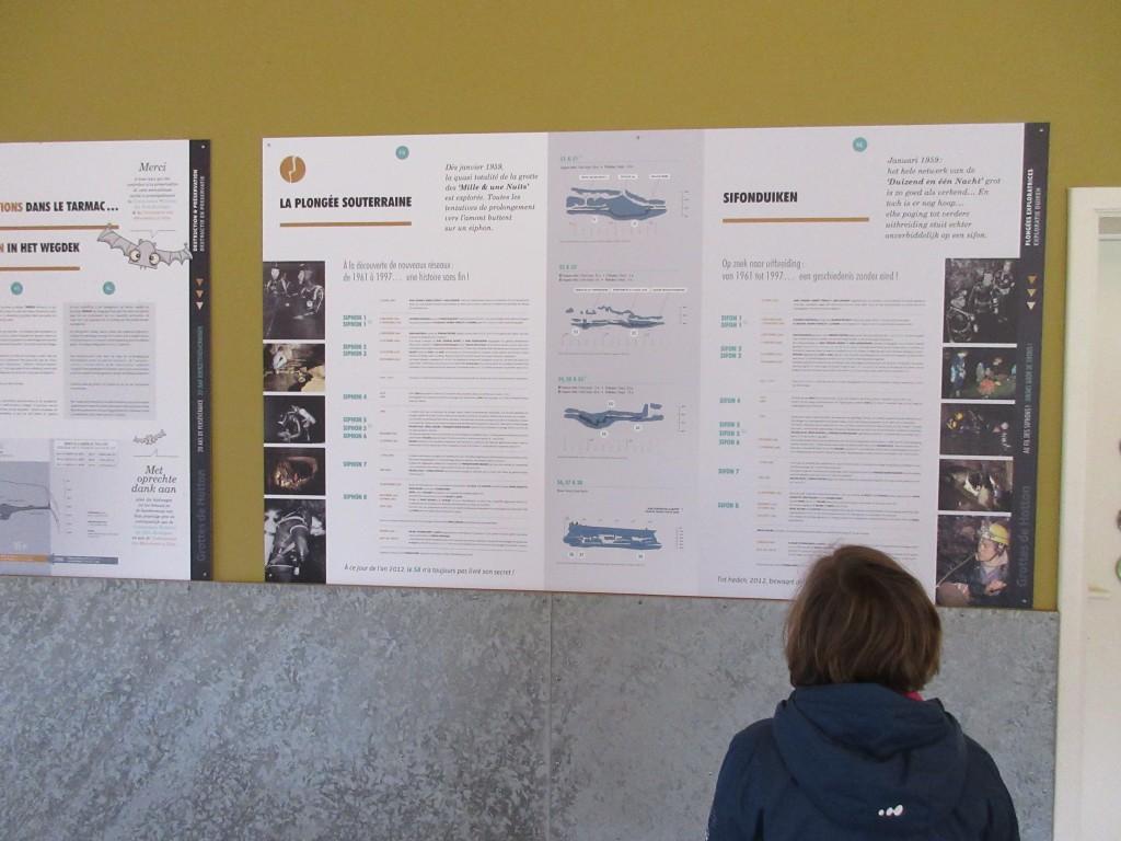 Aan de muur hangen grote borden boordevol informatie over de grotten van Hotton