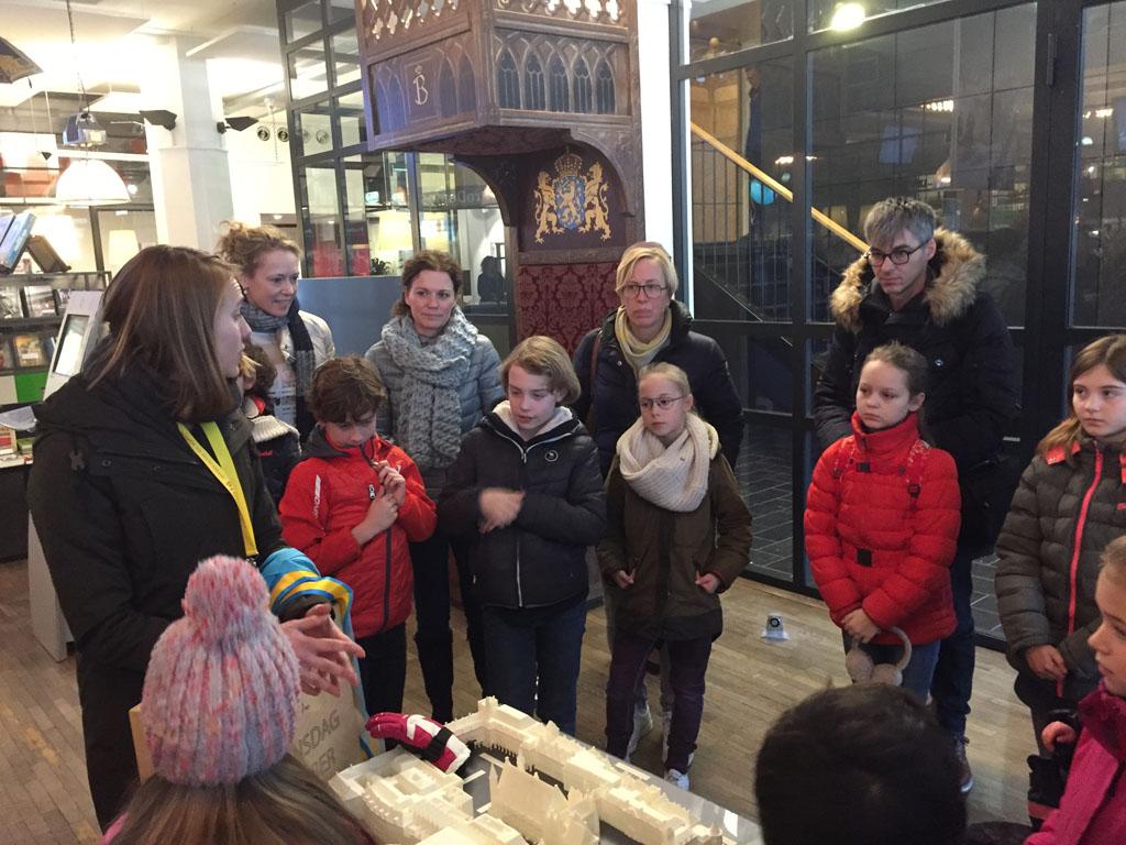 Bij ProDemos luisteren naar de inleiding van de kinderrondleiding in de Ridderzaal.