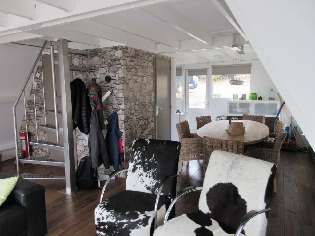 De woonkamer, eettafel en links de steile wenteltrap naar boven