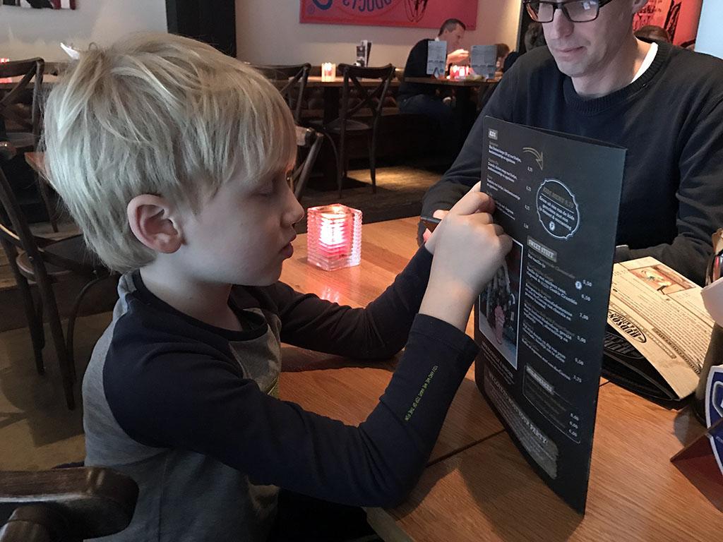 Op de menukaart kiest Tim wat van het kindermenu