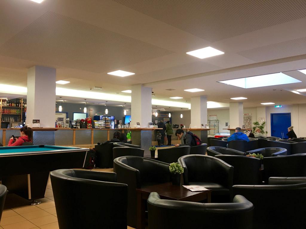 Aankomst in A&O Hostel Amsterdam Zuid-Oost in een grote lobby met bijvoorbeeld faciliteiten als kids corner en tafelvoetbalspel.