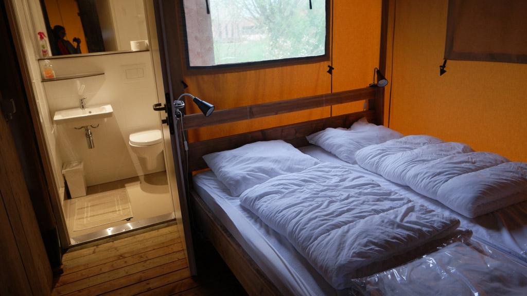 Het tweepersoonsbed en het badkamertje.