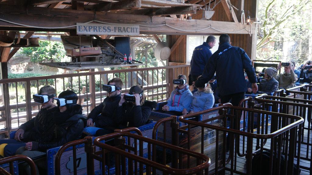 We zien mensen met een VR-bril in de achtbaan.