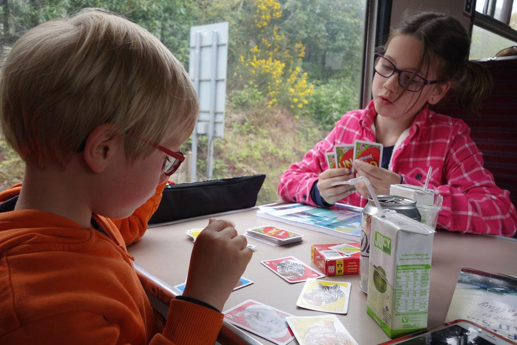 De kinderen zitten heerlijk in de trein en hebben alle ruimte om een spelletje te spelen, jacobite stoomtrein