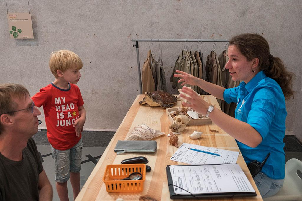 De enthousiaste medewerkster vertelt over de schelpen en schedels