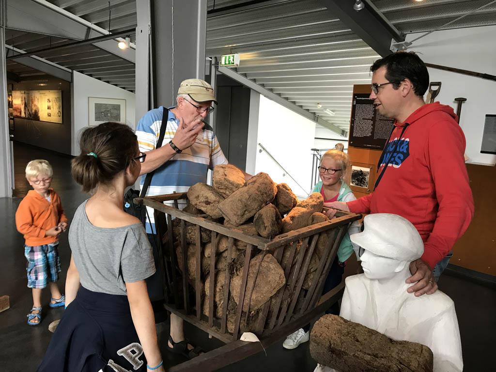 De kinderen mogen voelen hoe zwaar, of eigenlijk hoe licht, veen weegt in het Moor Museum in Emsland