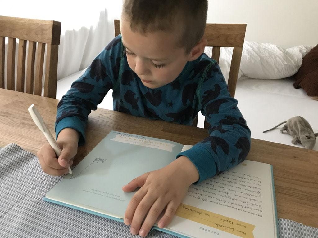 Camiel maakt zijn tekening aan tafel.
