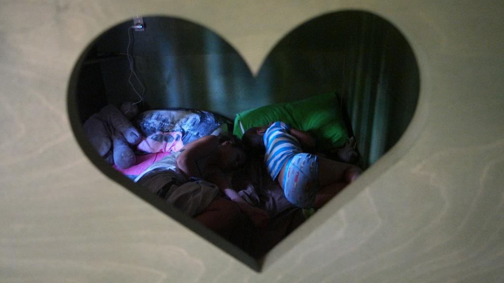 Twee slapende kinderen in de bedstee.
