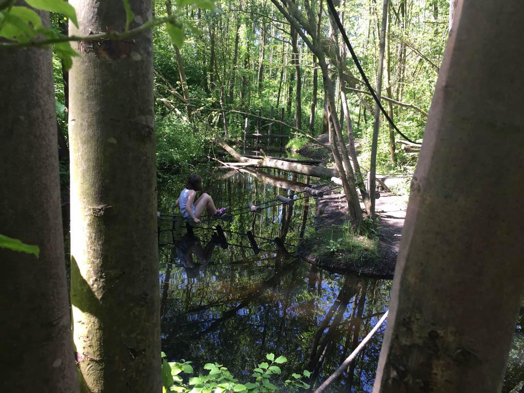 Maureen gaat via de touwen over het water.