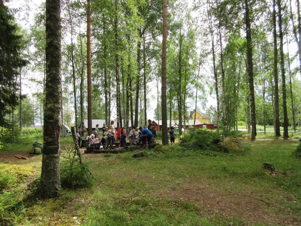 De groep verzamelt zich rond het kampvuur en krijgt uitleg over het verloop van de dag