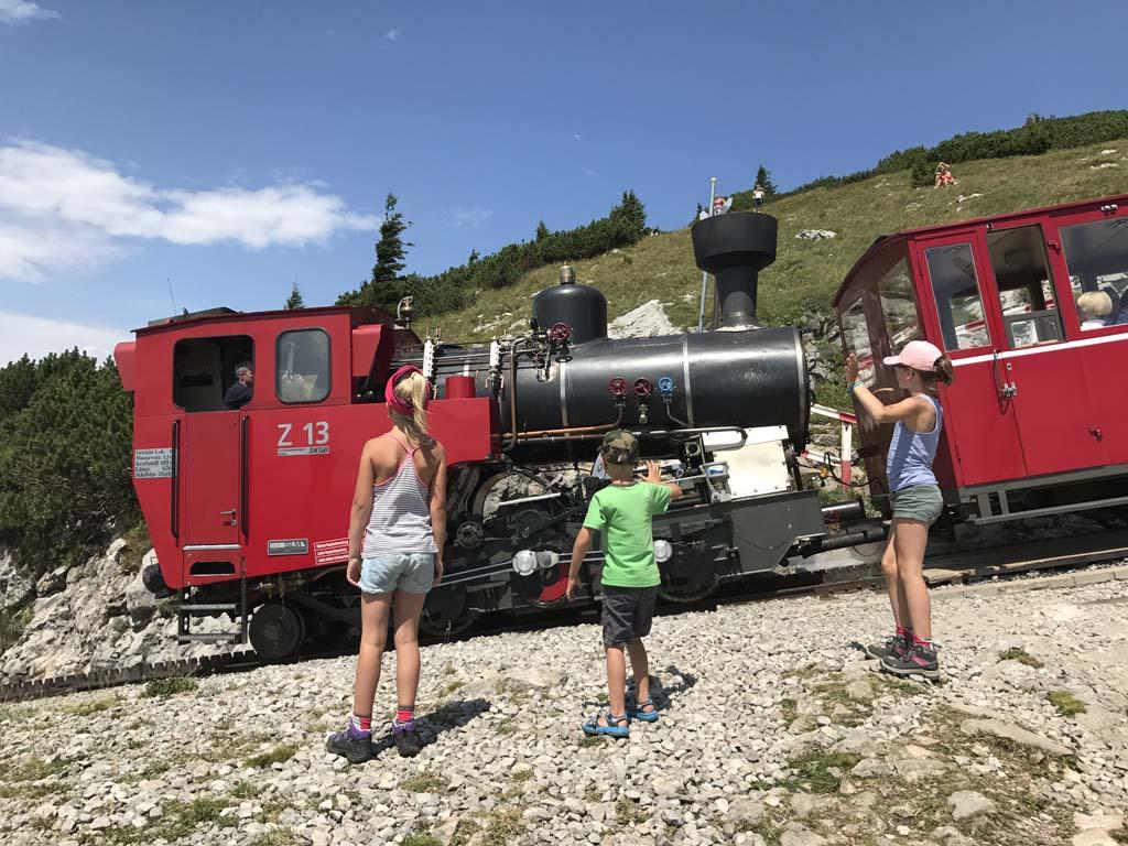 De locomotief duwt de trein de Schafberg op en is zelf een beetje schuin. Bij de Wolfgangsee