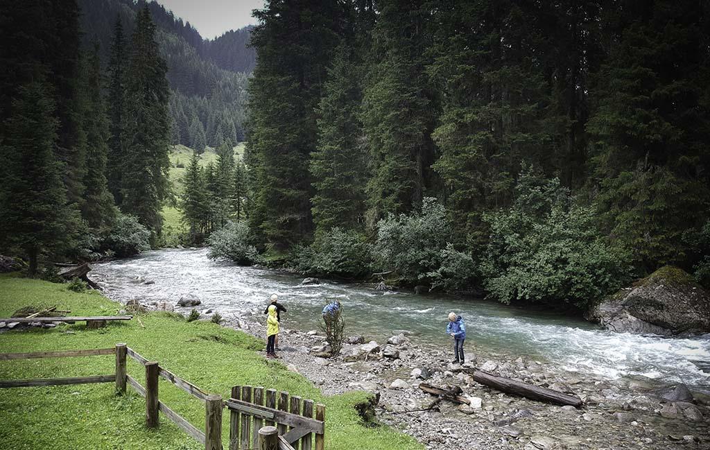 Ondanks de stromende regen, spelen de jongens toch in de rivier