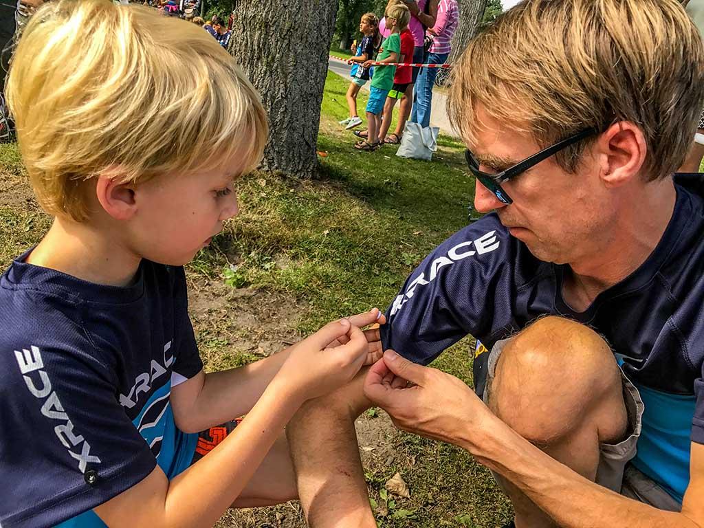 Tim naait een knoop op het shirt van zijn vader.