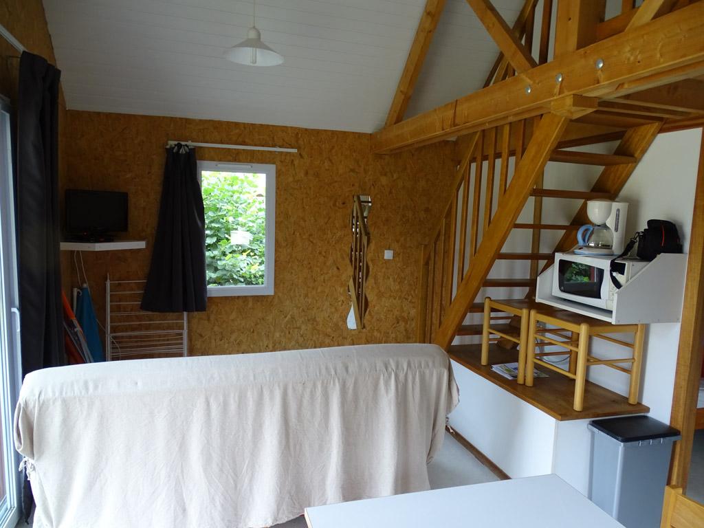 De woonkamer met keukentje, eethoek en slaapbank.