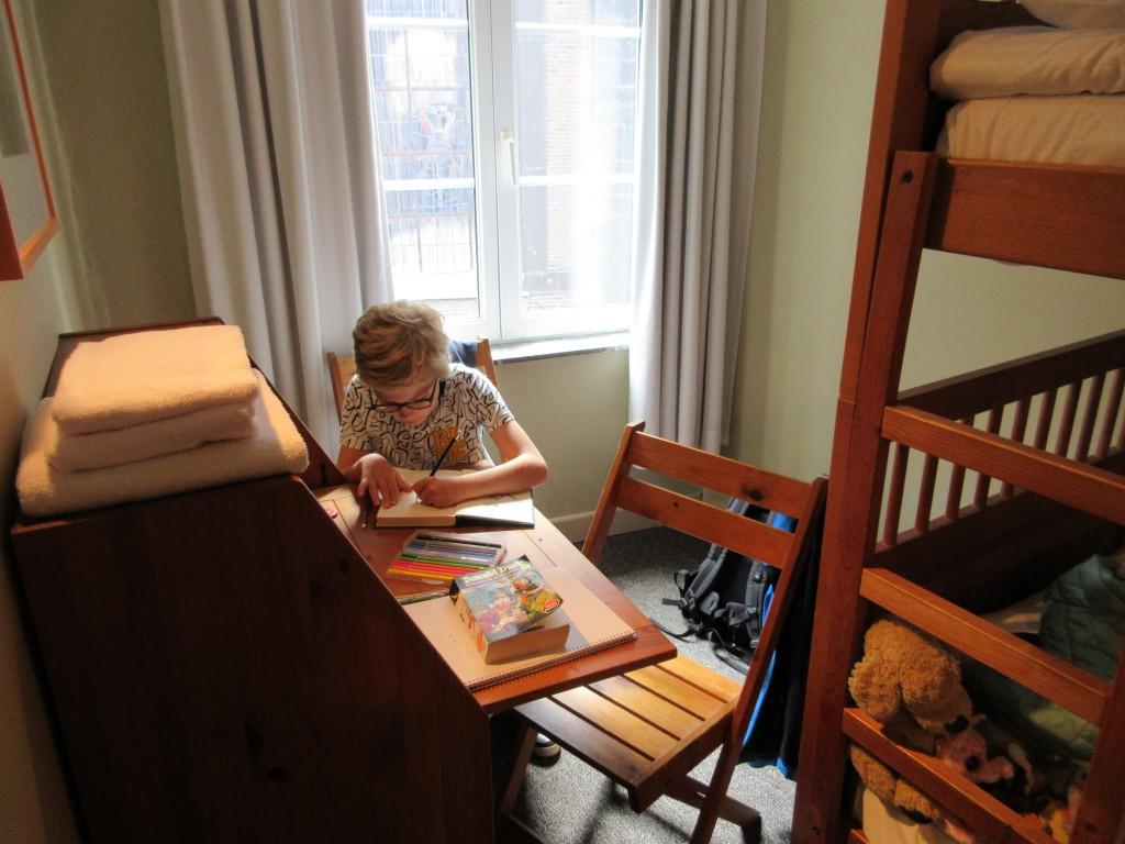 Tekenen aan het eigen bureautje in de familiekamer van Hotel les Tanneurs in Namen