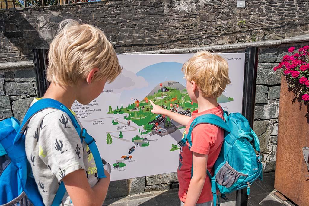 Bas en Tim bekijken bij het Fløibanen-station wat er te doen is op de Fløi-berg