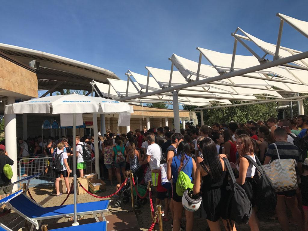 In de schaduw staat een lange rij voordat het aquapark open gaat.