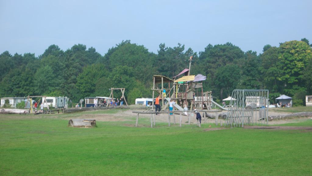 Het grote grasveld met speeltuin.
