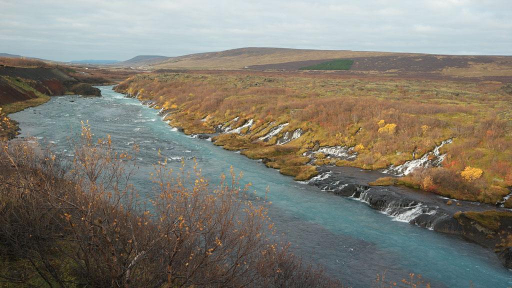Bij Hraunfossar komt het water halverwege uit de rotswand.