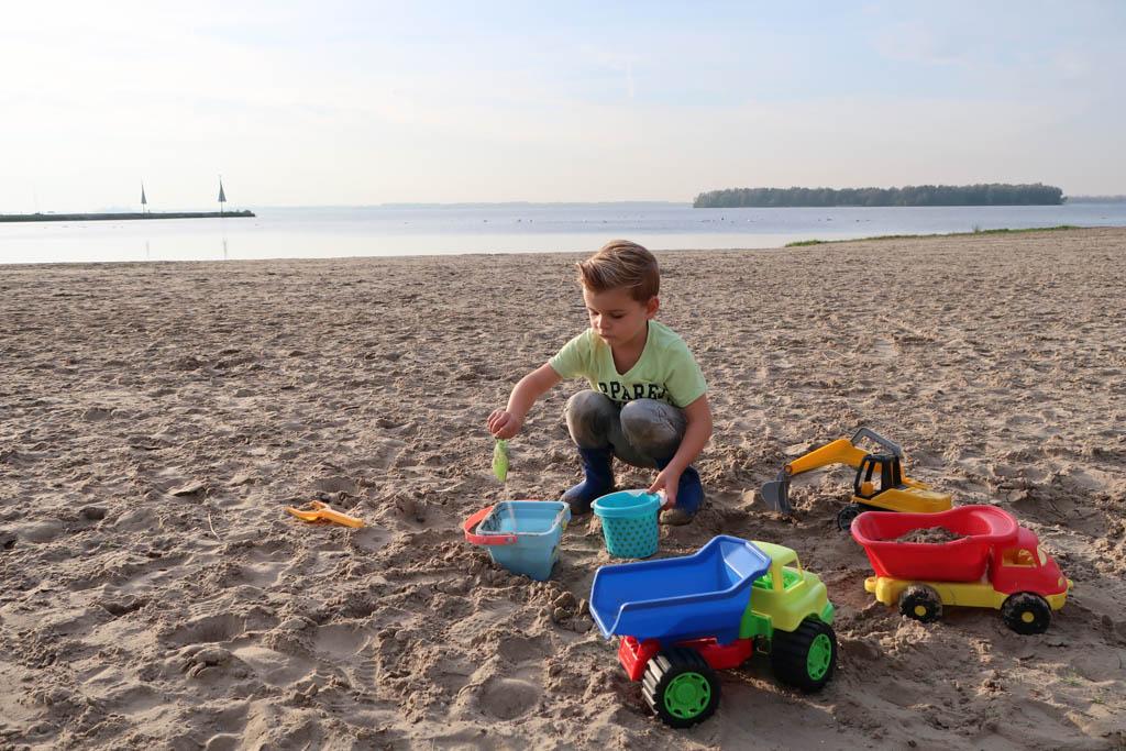 Mats vermaakt zich prima op het strand voor het huisje op Droompark Bad Hulckesteijn.
