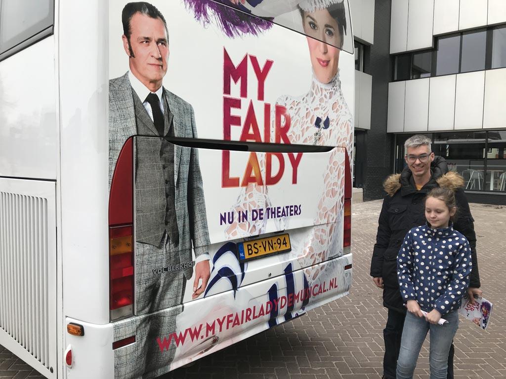 De bus van de cast staat bij het theater.
