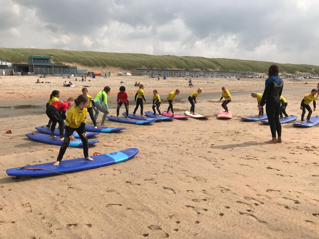 Leren surfen tijdens een vakantiekamp zorgt gegarandeerd voor sterke verhalen bij thuiskomst.