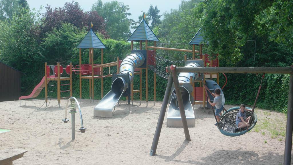 De speeltuin, met links de grappige wip en rechts lol op de schommel.