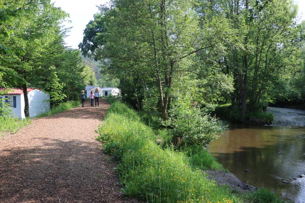Het riviertje van de camping wordt door een wat hoger wandelpad gescheiden van de kampeerplaatsen en accommodaties.