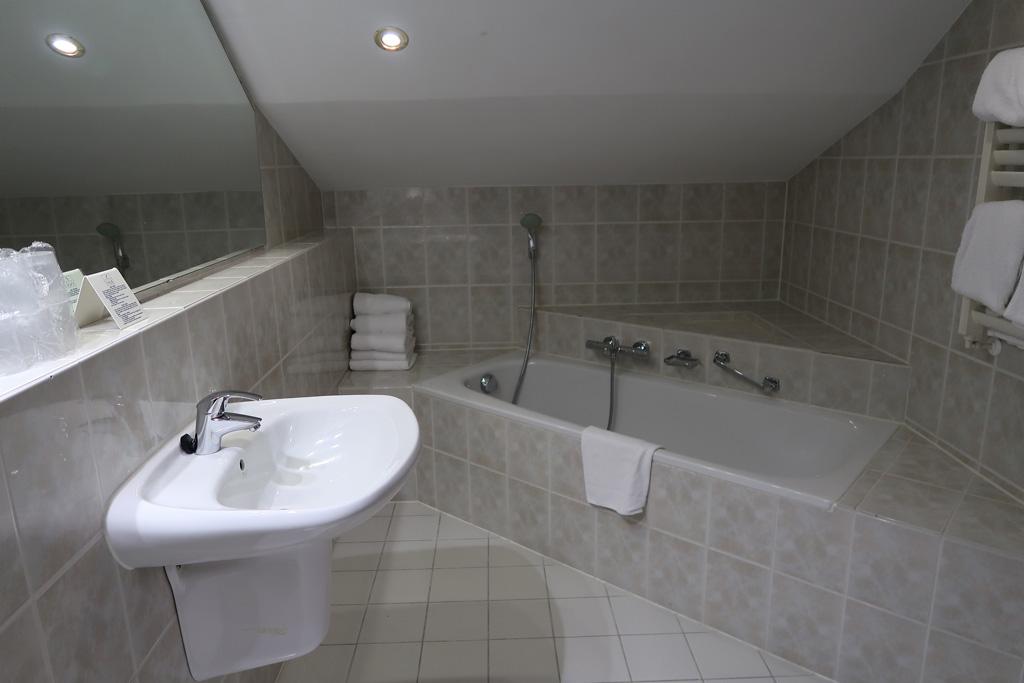 Ook de badkamer is ruim en voorzien van bad, toilet en douche.