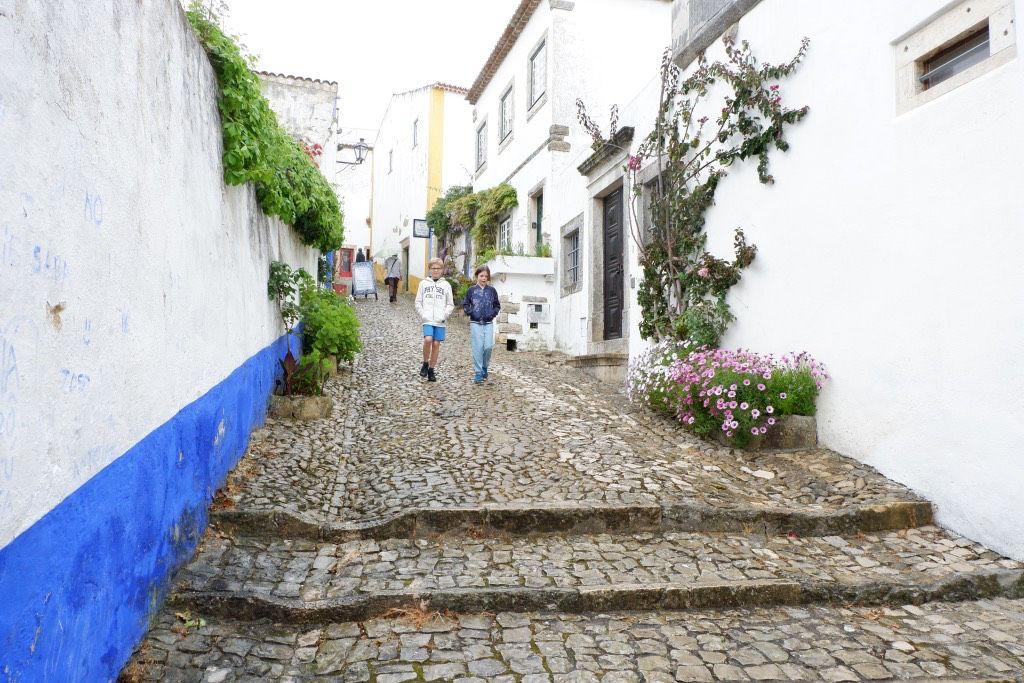 Wandelen door de straatjes van Óbidos, langs de witte muren met blauwe randen