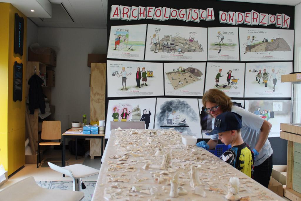 Een tafel vol scherven en uitleg van een echte archeoloog in Castellum Hoge Woerd.