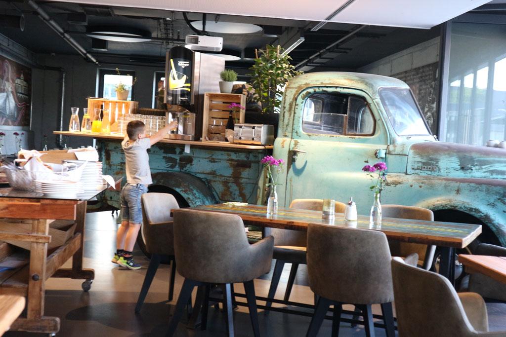 Een deel van het ontbijtbuffet staat op de laadbak van een oude auto.