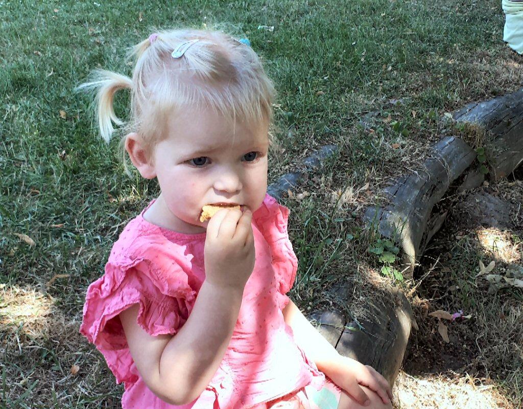 Olivia geniet van een verse koek op de biologische markt