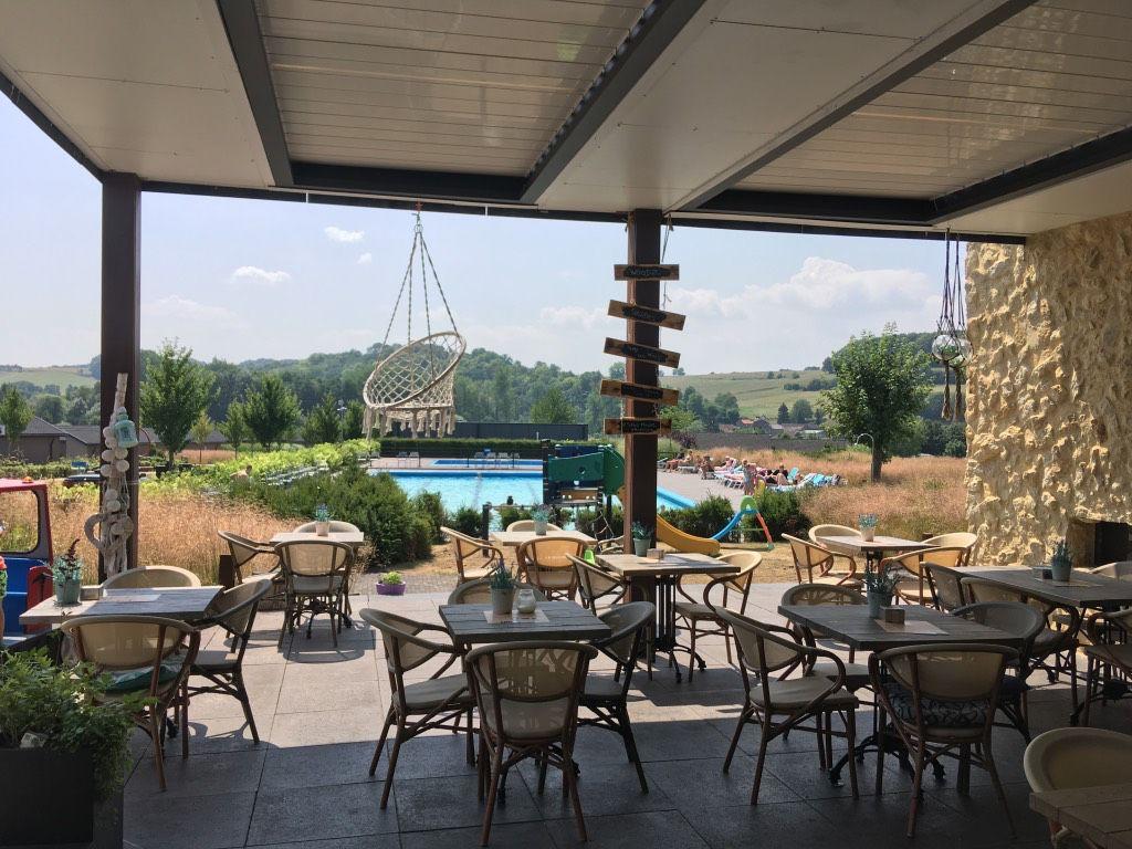 Openluchtzwembad in Zuid-Limburg? Vanaf het terras kijk je hoe de kinderen zwemmen bij restaurant Woodz
