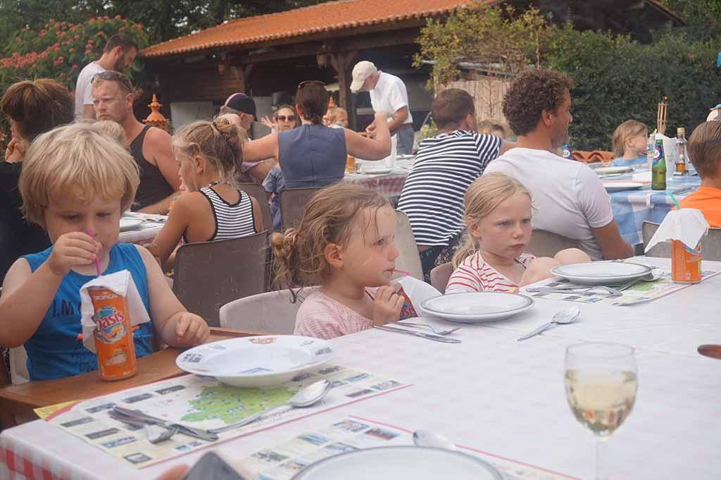 De campinggasten schuiven aan grote tafels bij elkaar aan