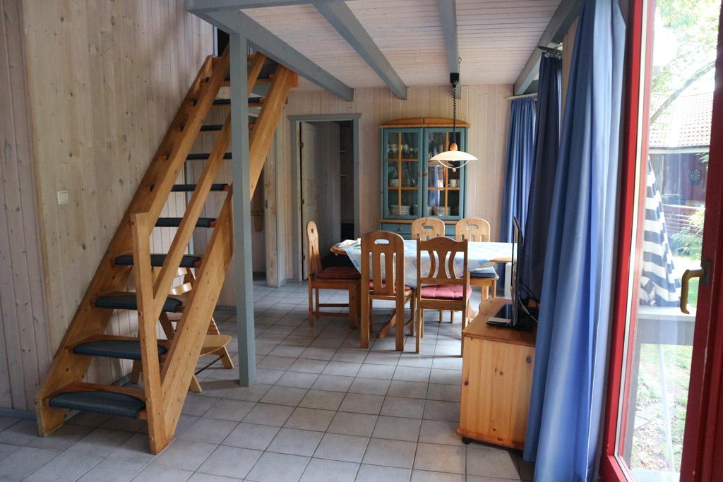 Vanuit de woonkamer zicht op de eethoek en de trap naar boven.