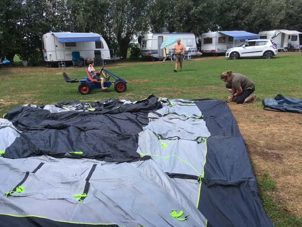 We leggen de tent op de grond en zetten de hoeken met haringen vast.